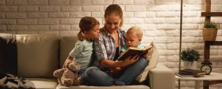 A family sitting on a sofa in the evening, reading a book together.